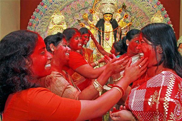 Married women participate in the ritual of 'Sindur Khela' at a Durga Puja pandal in Birbhum, West-Bengal. (Image: Archive.indianexpress.com)